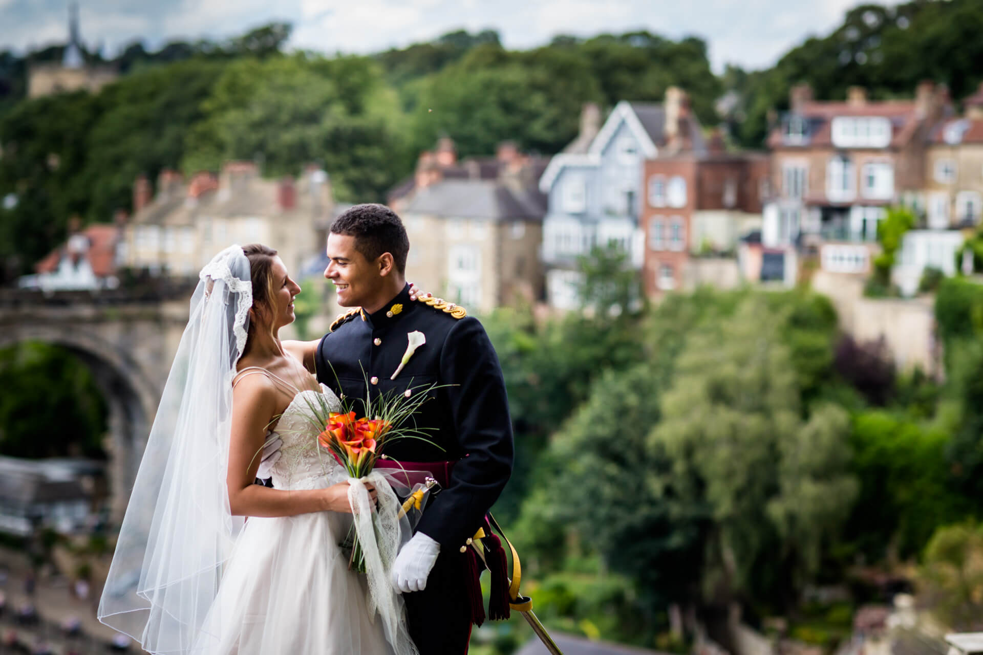 bride and room look at each other in front of a beautiful view of Knaresborough