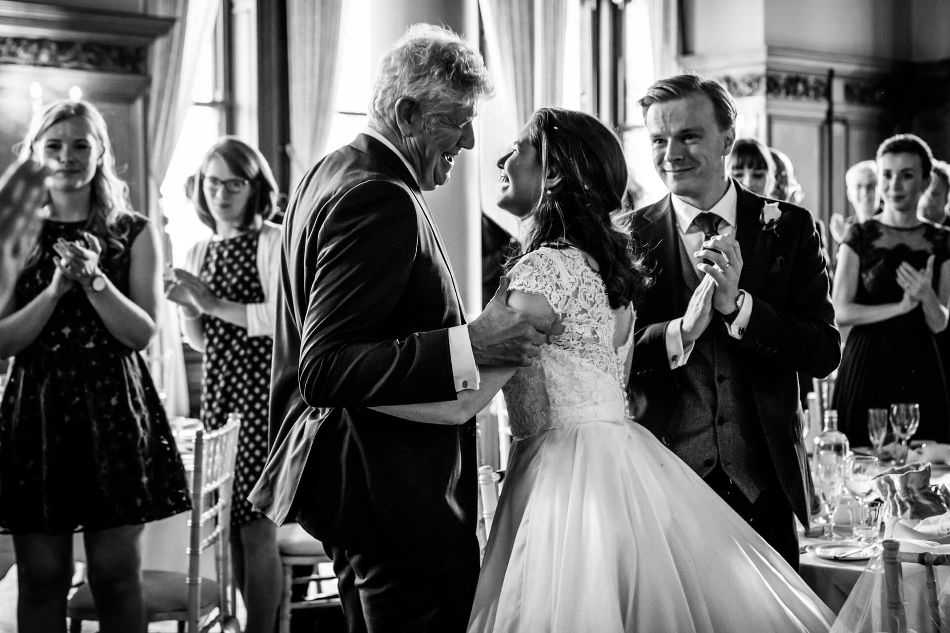 bride and her dan laugh together as the wedding guests clap