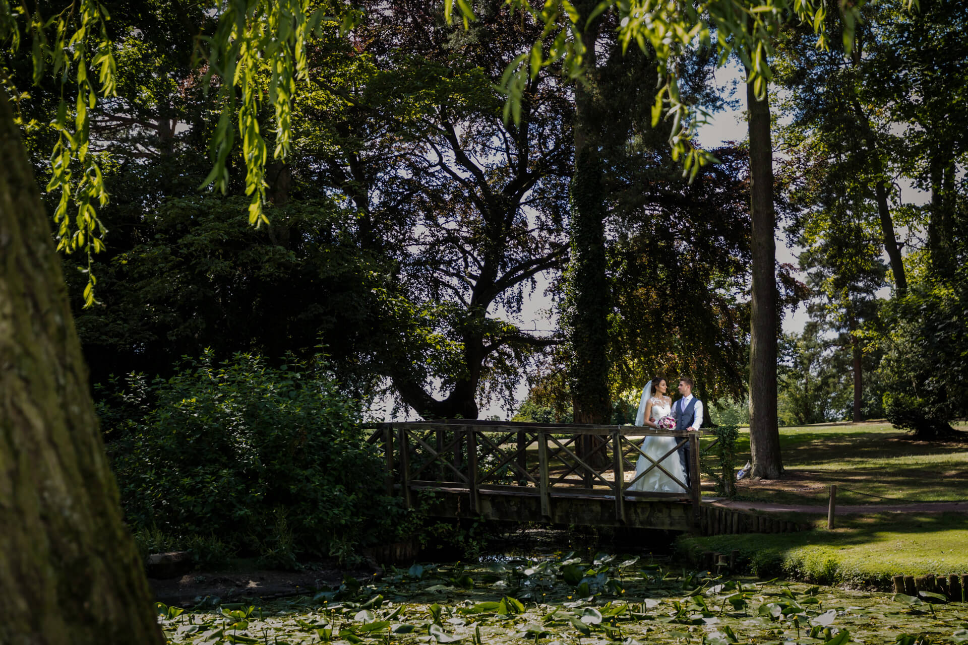 bride and groom stand together in the gardens of Aldwark manor