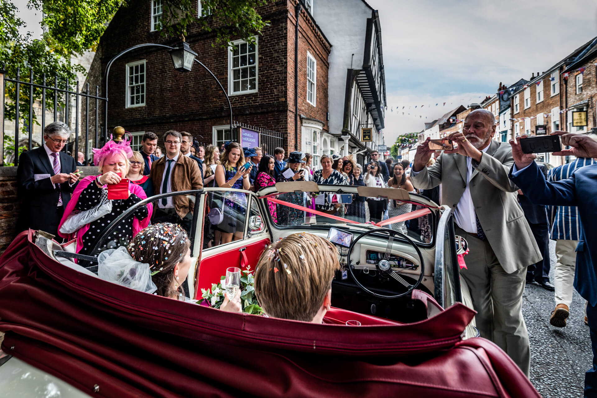 wedding couple sat in their wedding car whilst guests take photos of them