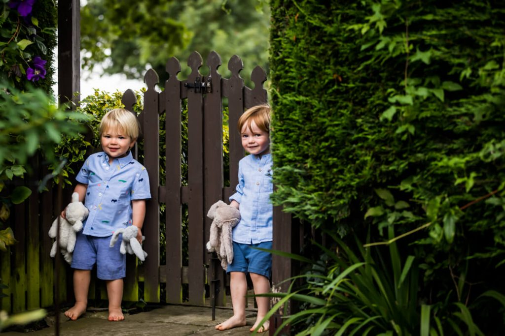 two little boys giggling behind a fence