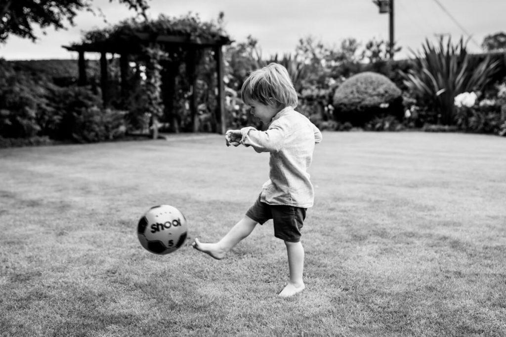 toddler kicking a football in his garden