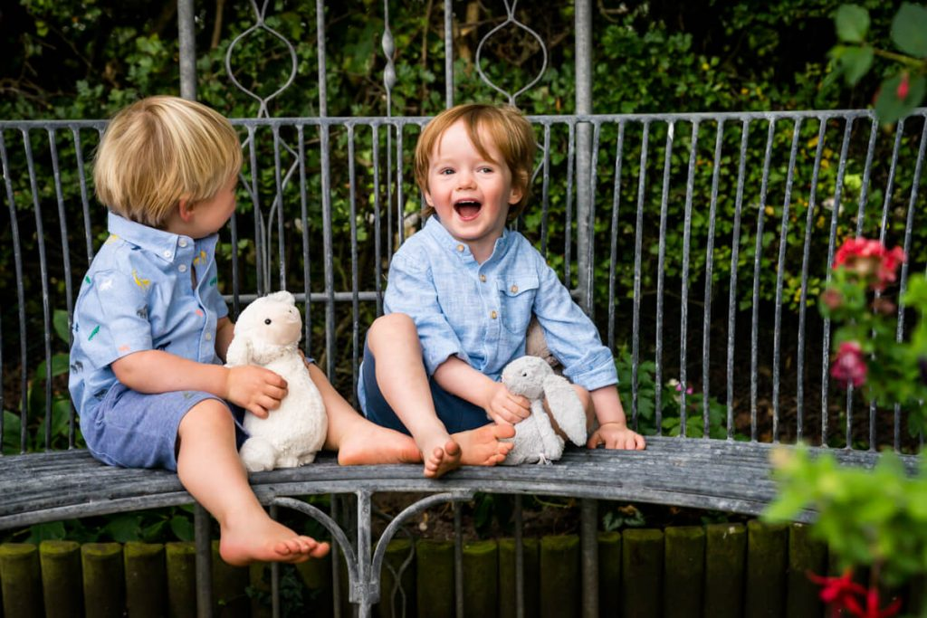 two small boys sitting together and laughing