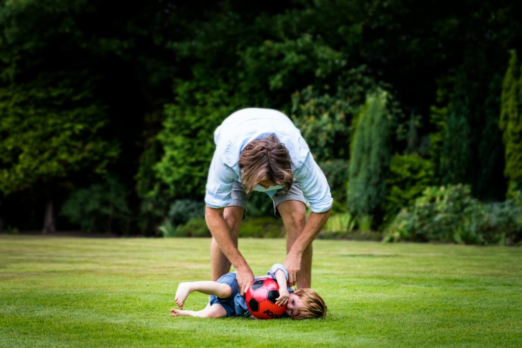 dad tickling his son as he lies on the grass clothing his football
