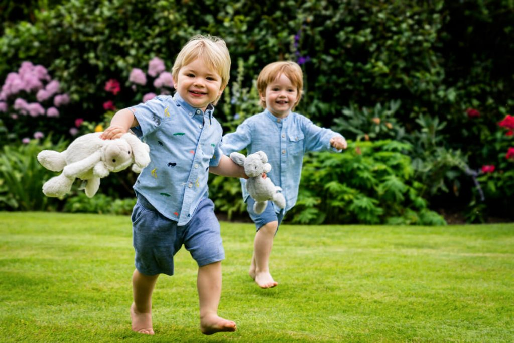 two toddlers running with their teddy bears