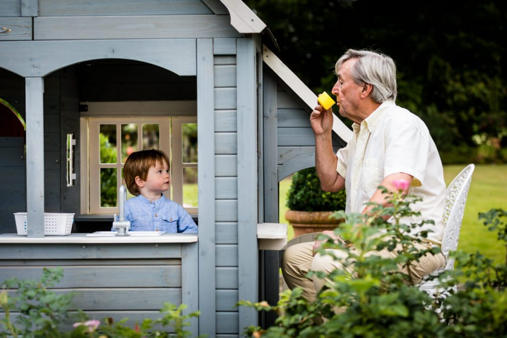 little boy serving tea to his grandfather from his play house