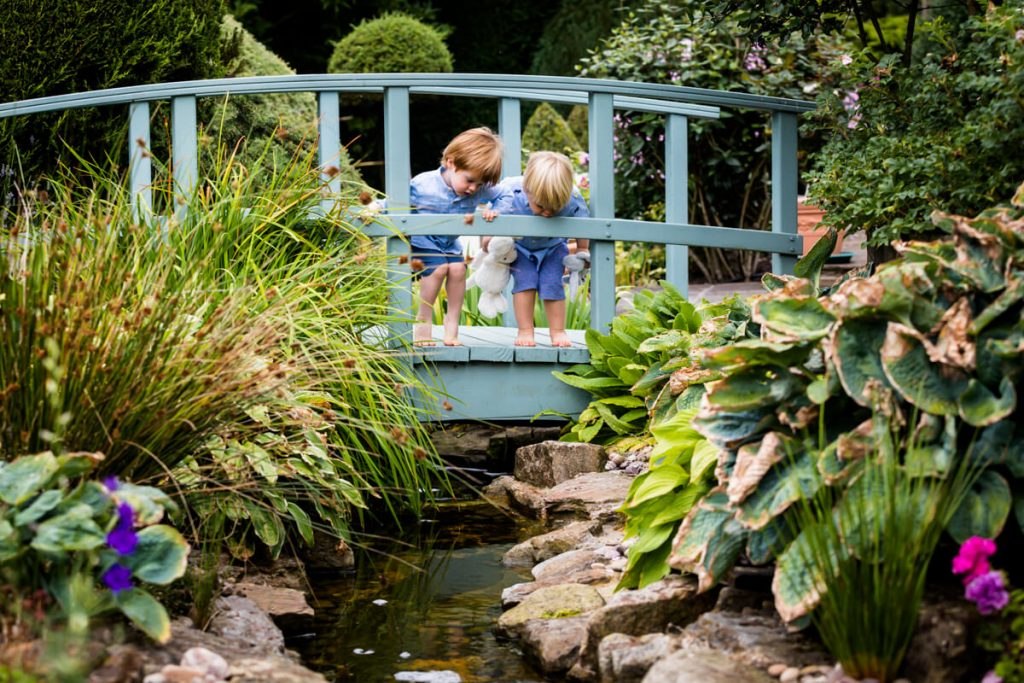 two little boys looking over a bridge down at a river