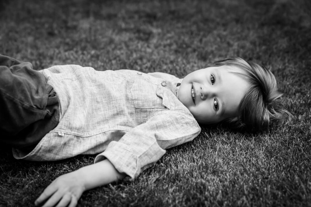toddler lying on the grass and smiling