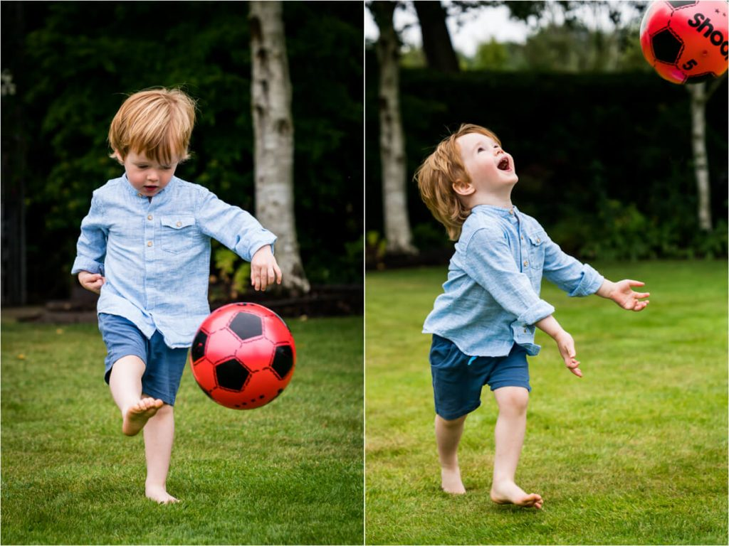 Little boy paying football in a family garden in yorkshire