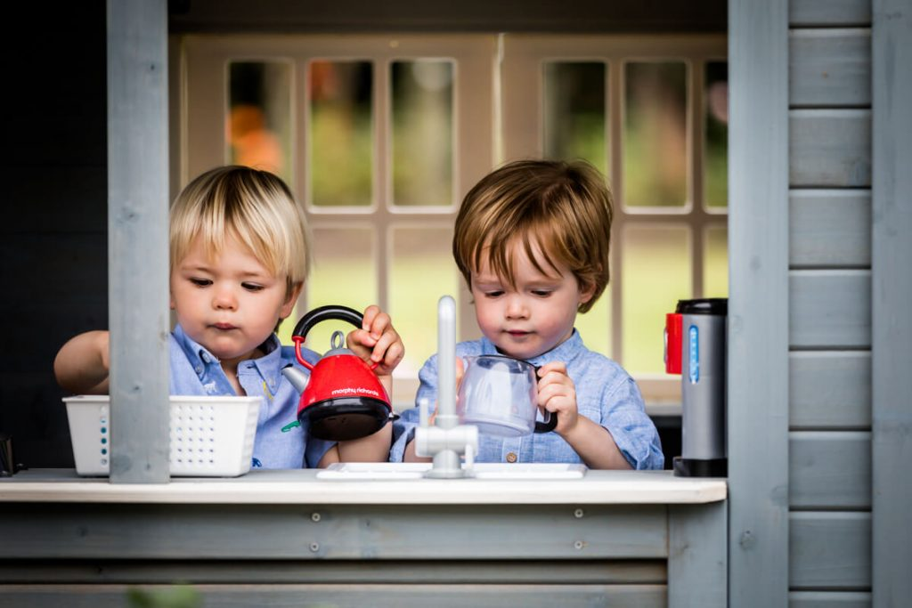 two little boys in their playhouse in a Yorkshire garden
