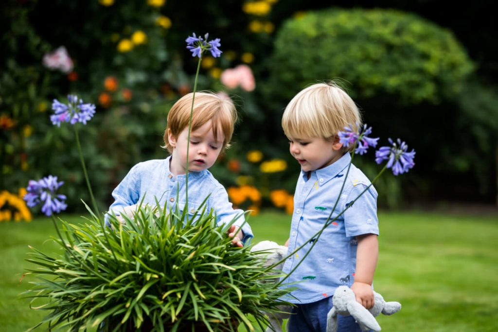 two little boys looking at some flowers