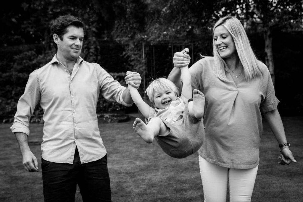 mum and dad swinging their little boy