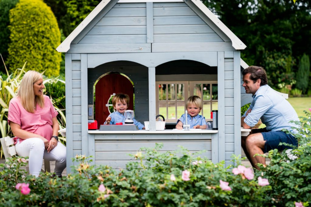 two little boys in their play house with mum and dad watching