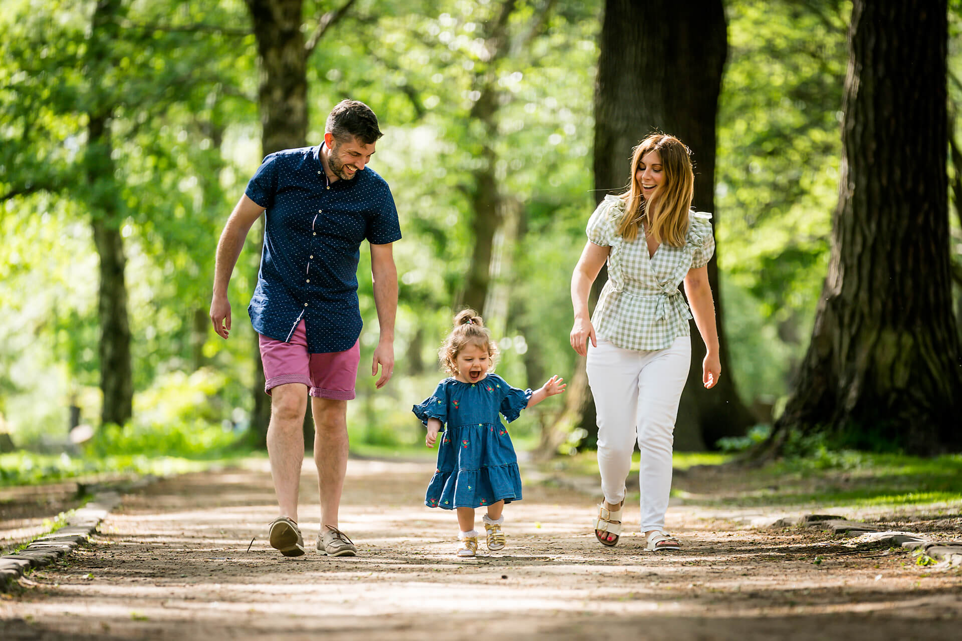 mum and dad walking with their toddler at golden acre park in leeds