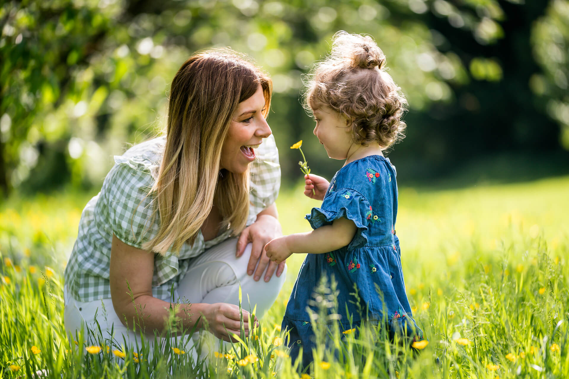 little girl showing a flower to her mother in a leeds park