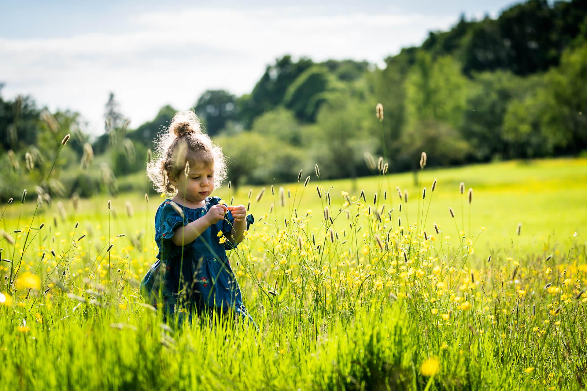 little girl picking flowers in a leeds park