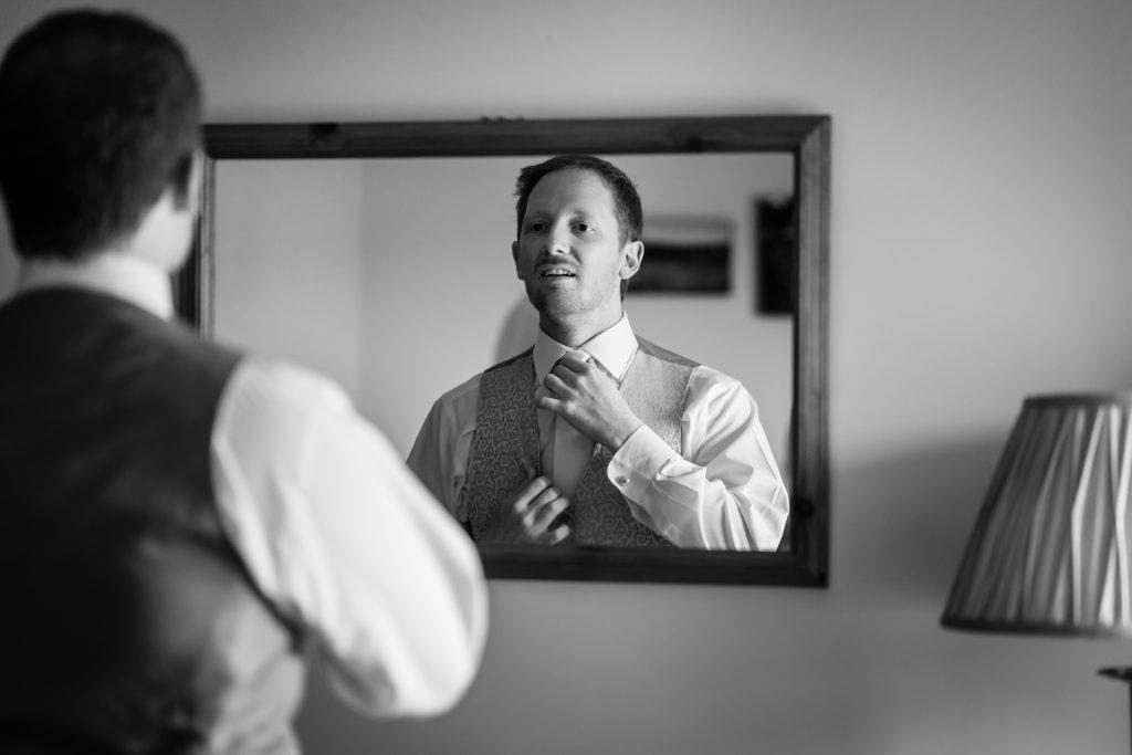 groom adjusts his tie in a mirror