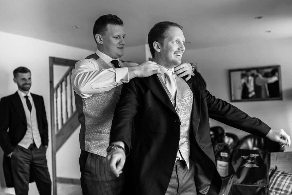 best man helps groom with his jacket