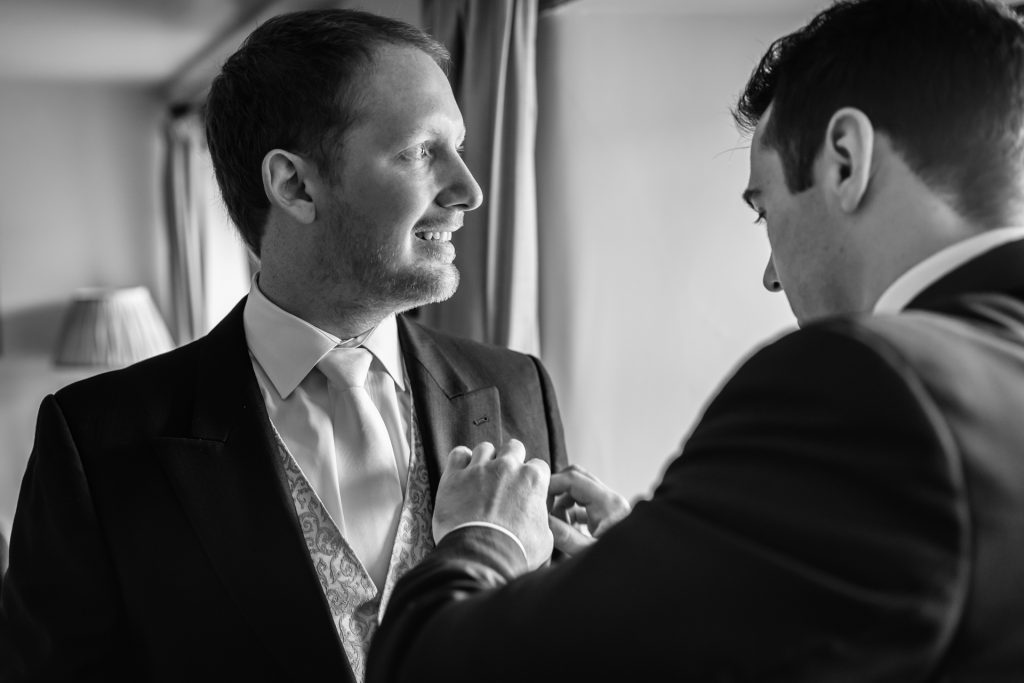 best man fixes the grooms buttonhole
