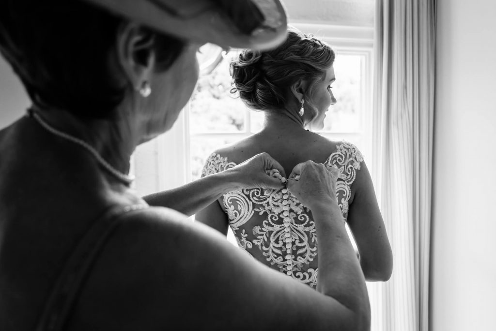 mother of the bride doing up the brides dress