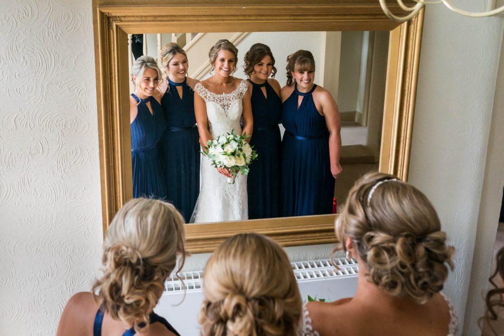 bride and bridesmaids looking in a mirror