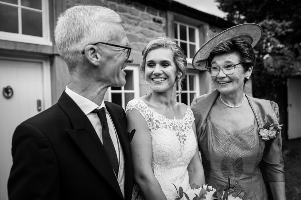 bride standing with her mother and father