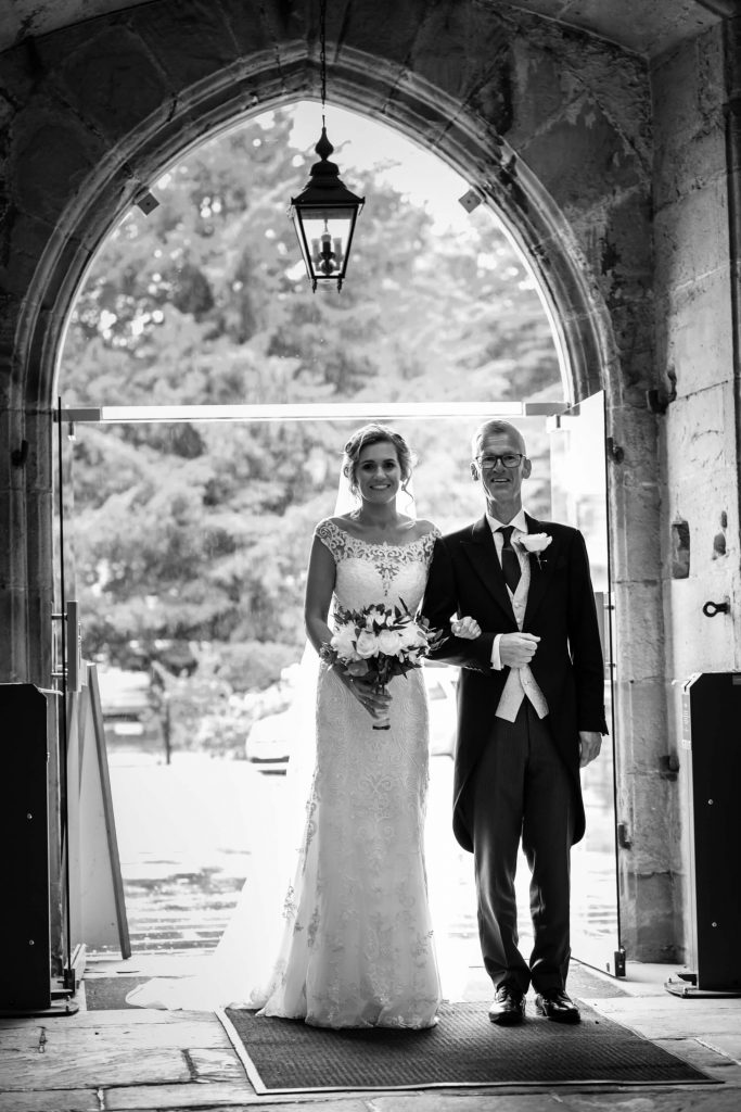 bride and her father under the church door archway