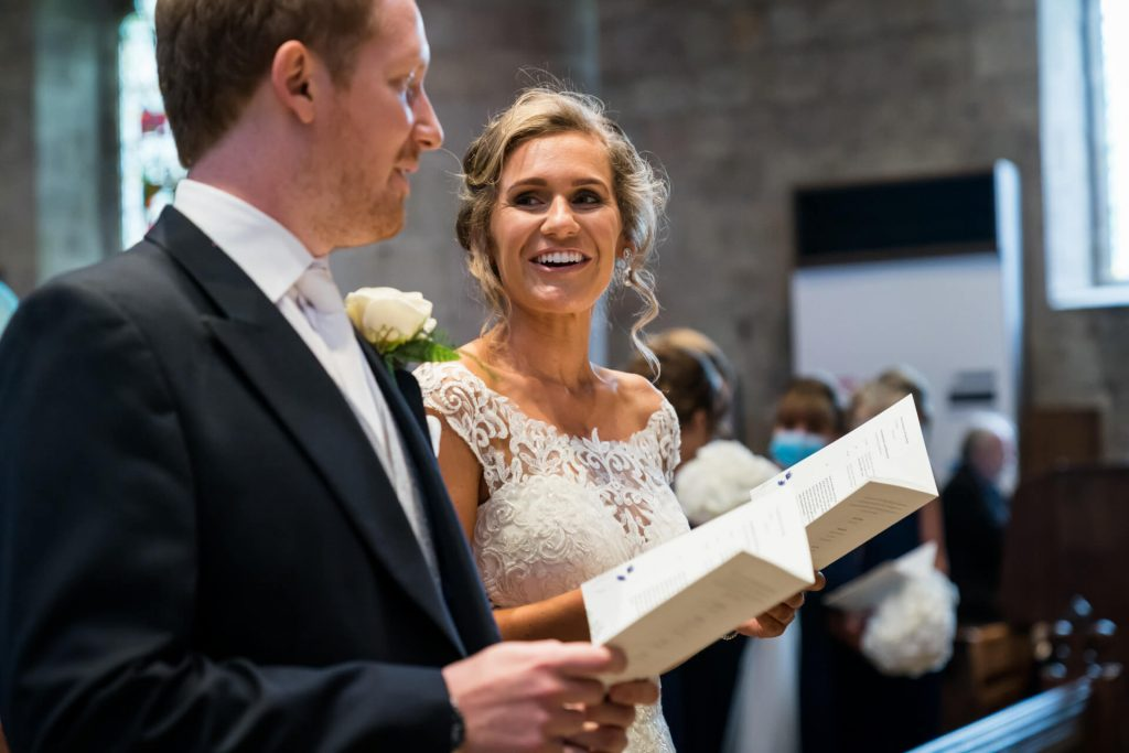 bride looking at the groom whilst singing a hymn