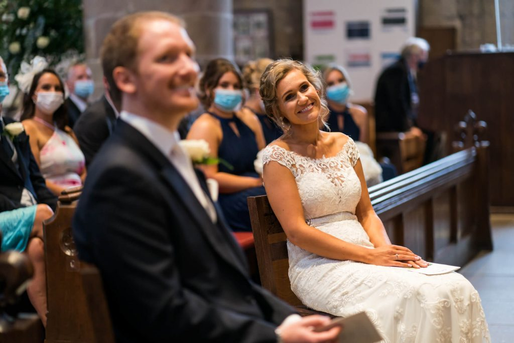 bride and groom smiling at the front of the church