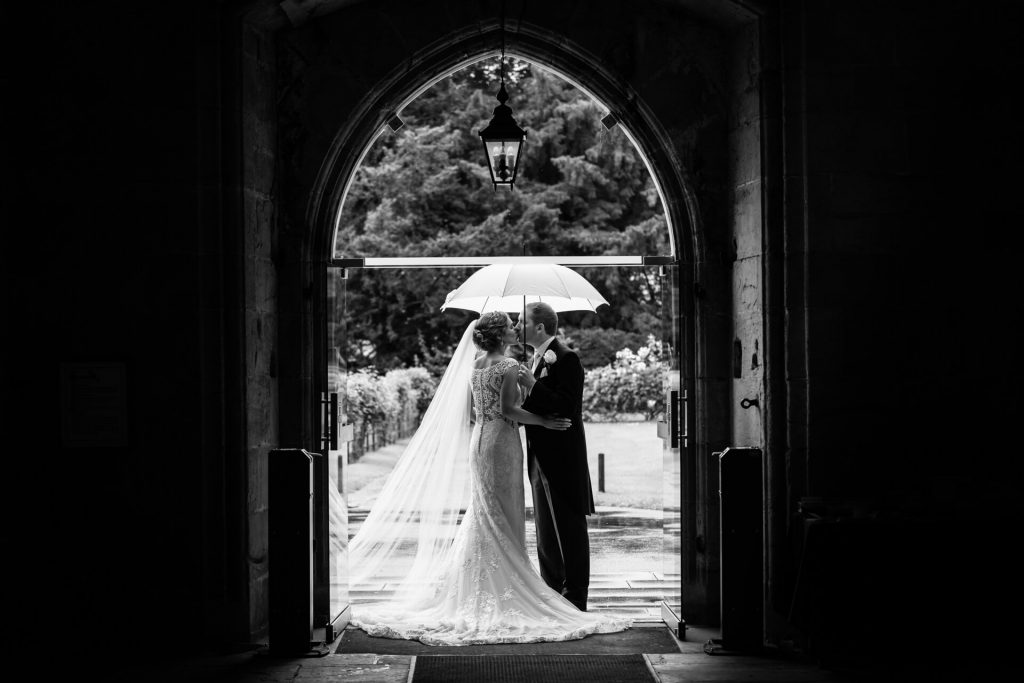 bride and groom kiss in the doorway of Bolton Abbey