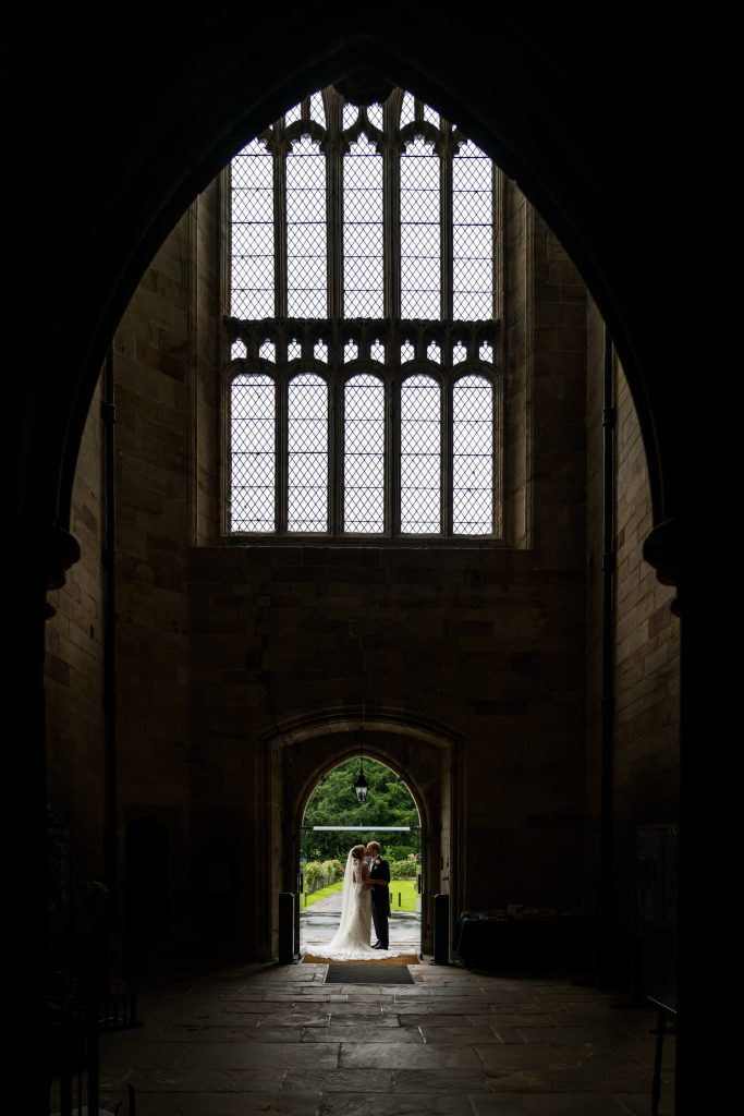 bride and groom under the Bolton Abbey arch