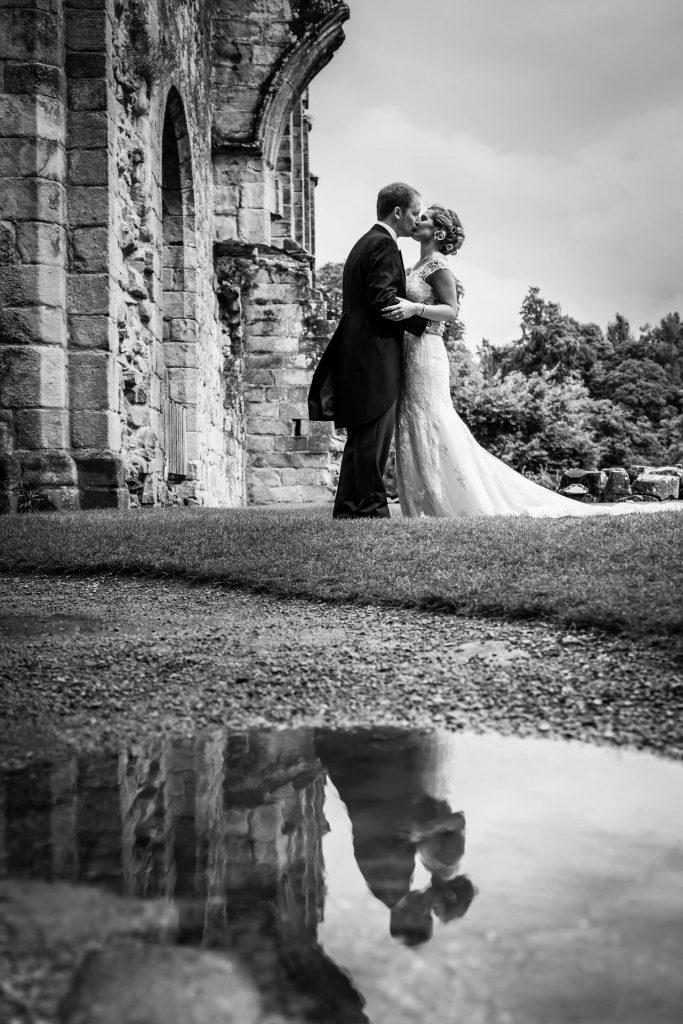 puddle reflection of the bride and groom kissing