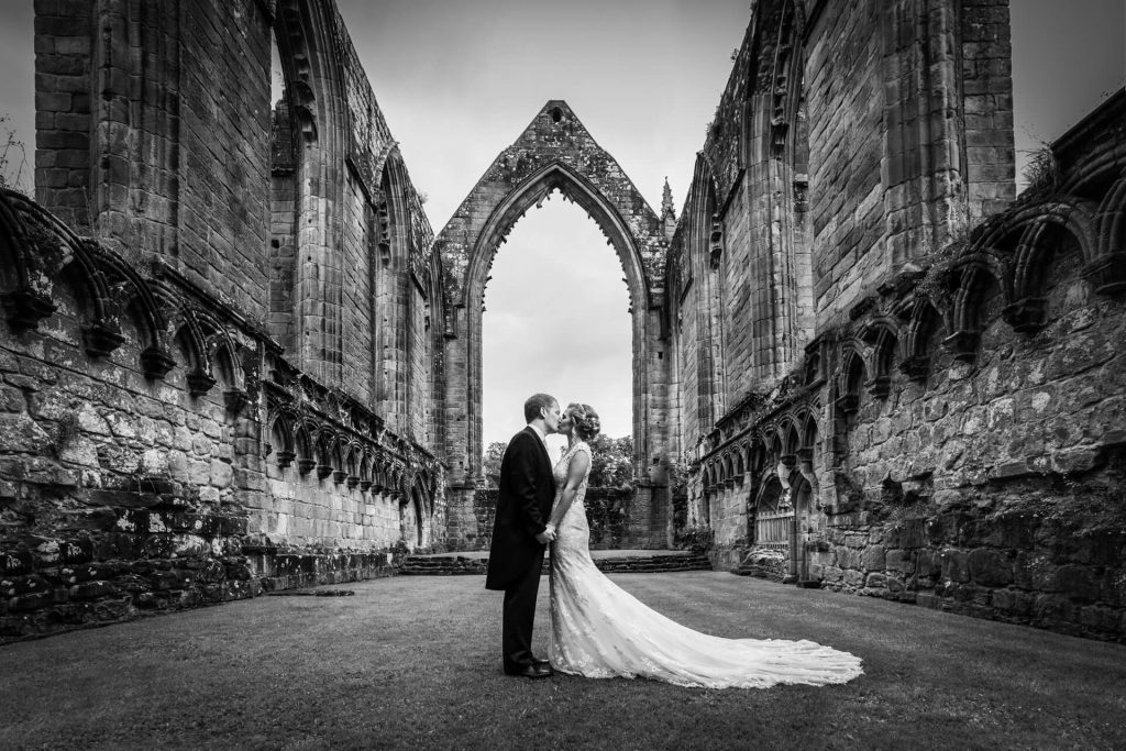 Bolton Abbey wedding couple kissing under an archway