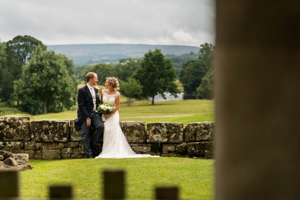 bride and groom sitting on a wall in front of view