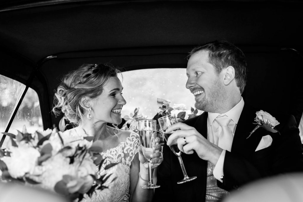 bride and groom having a toast in the wedding car