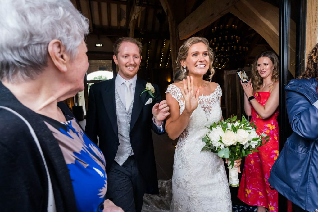 bride and groom walk out of the doors at Tithe Barn