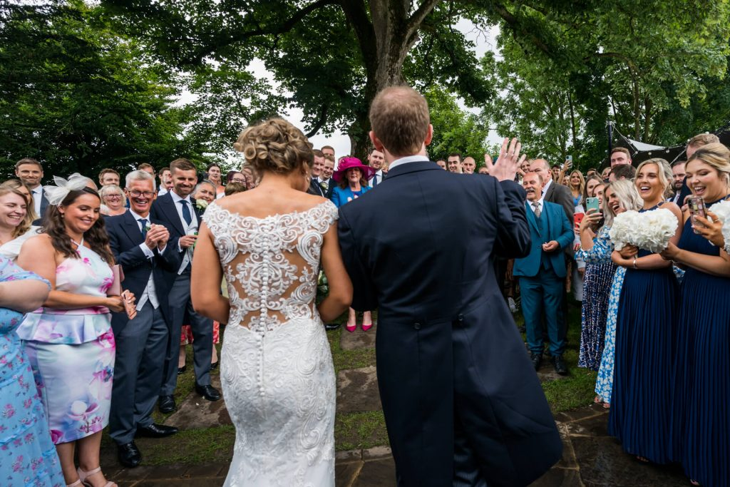 bride and groom waving to their guests