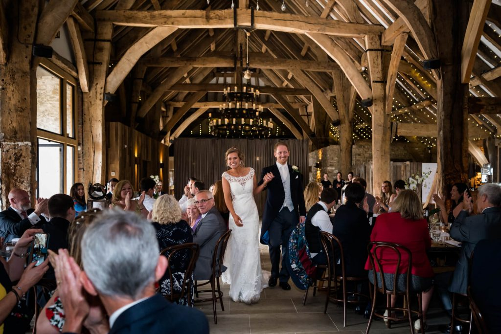 bride and groom walk into their wedding reception