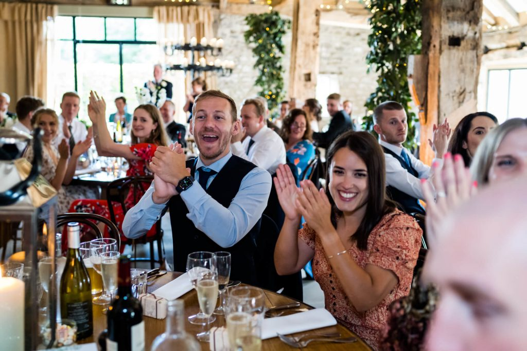 guests clapping whilst wedding couple walks in