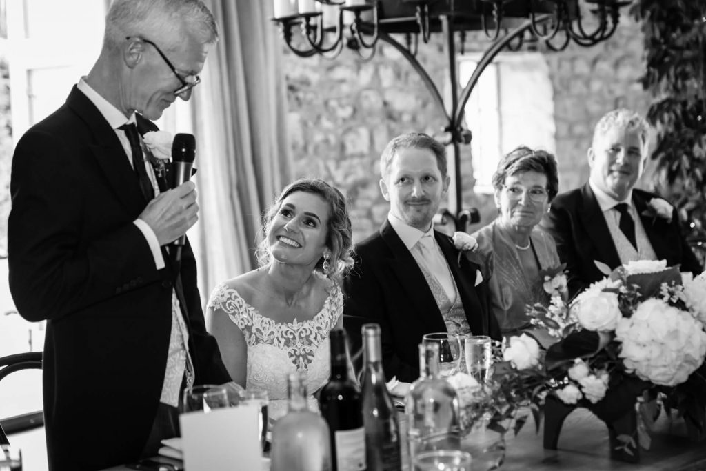 bride looking at her father whilst he gives his wedding speech