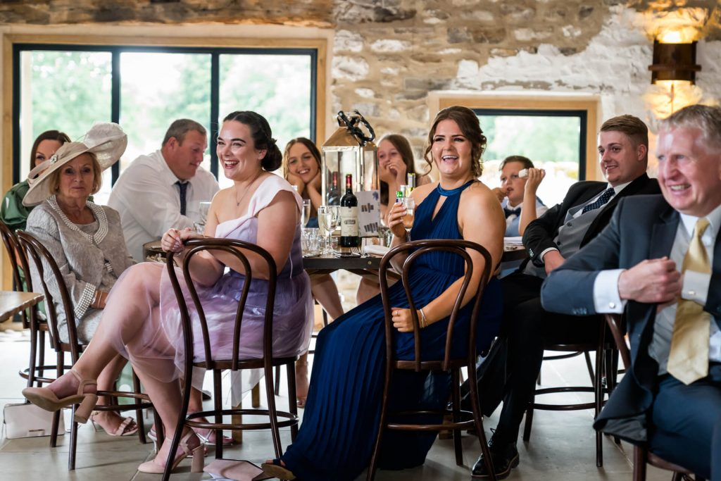 guests laughing during the wedding speeches