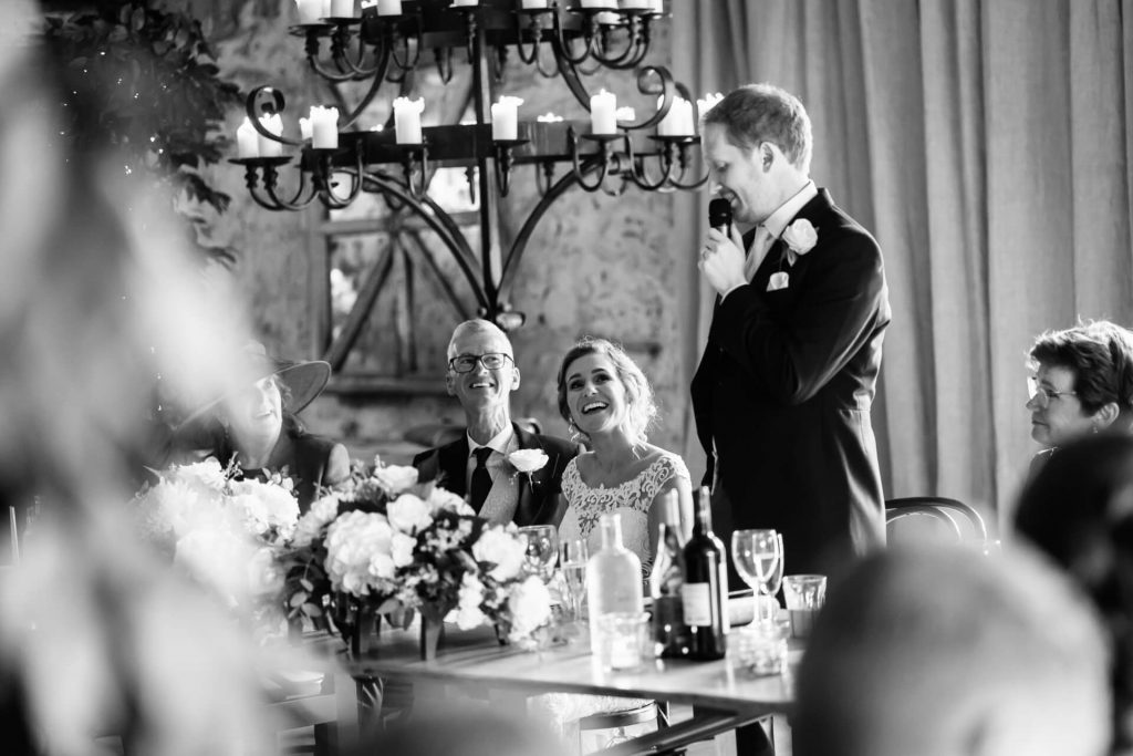 bride laughing whilst the groom speaks