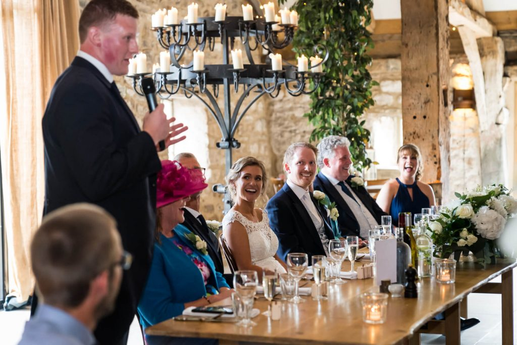 wedding party laughs whilst the best man speaks