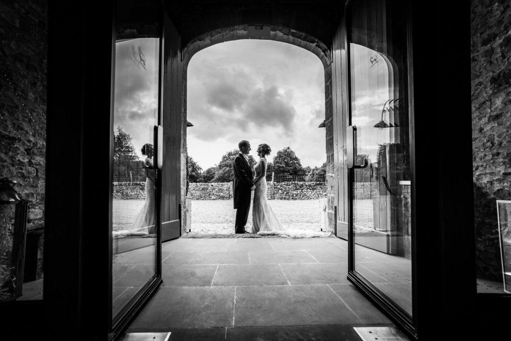 bride and groom in the doorway of Tithe Barn