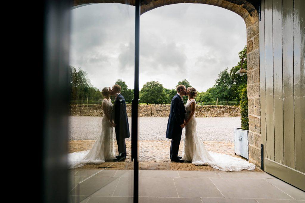bride and groom kissing in the barn doorway