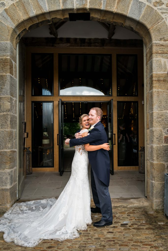 bride and groom laughing in the doorway of Tither Barn