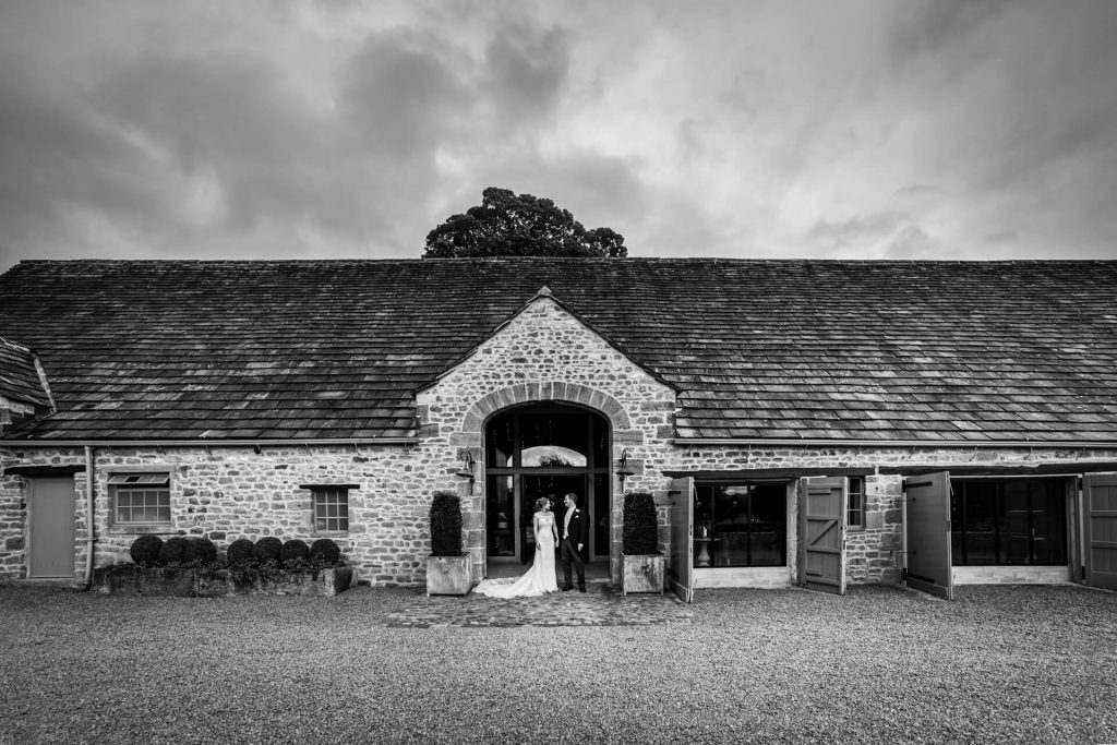 bride and groom portrait in front of Tithe Barn