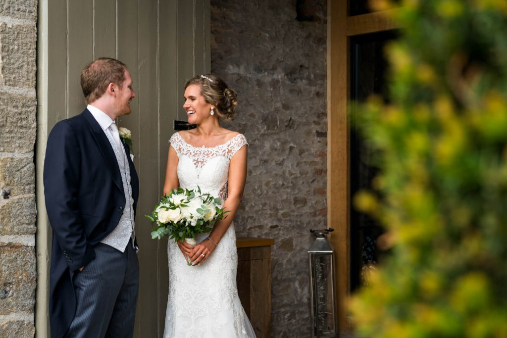 bride and groom laughing together in a doorway
