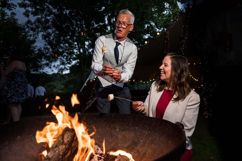father of the bride toasting some marshmallows